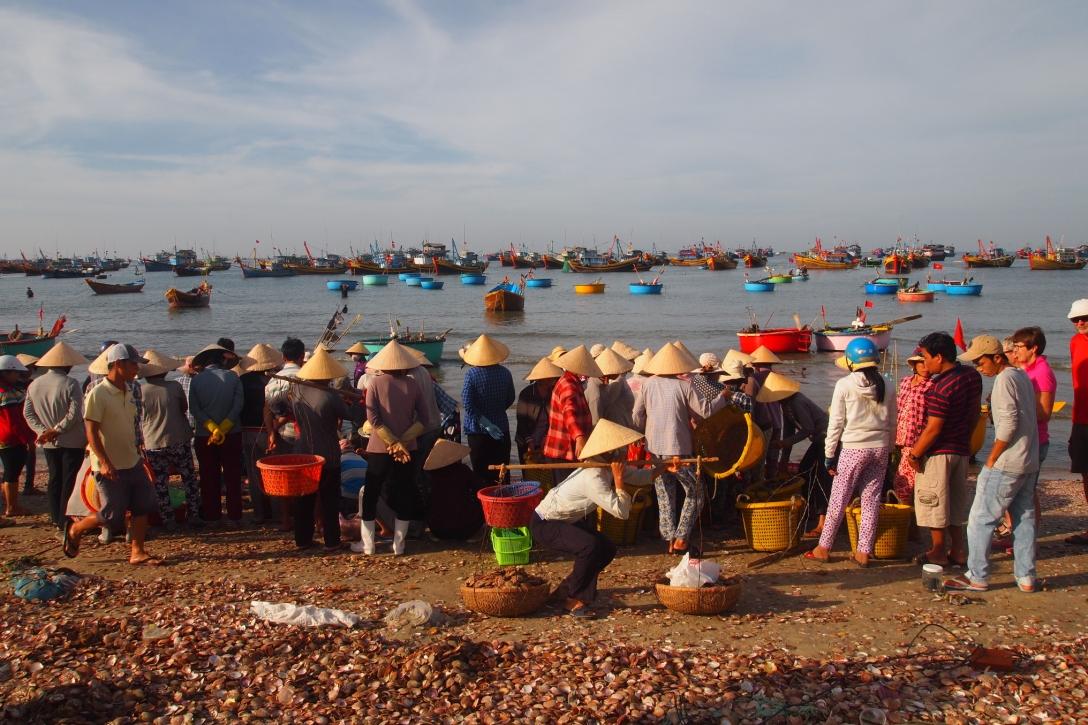 Frauen nehmen den Fang der Fischer entgegen und tragen ihn weg.